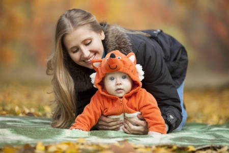 Young woman with baby dressed in fox costume having fun in autumn park photo