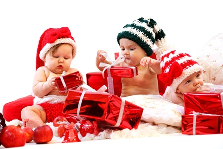 Three babies in xmas costumes playing with gifts over white background