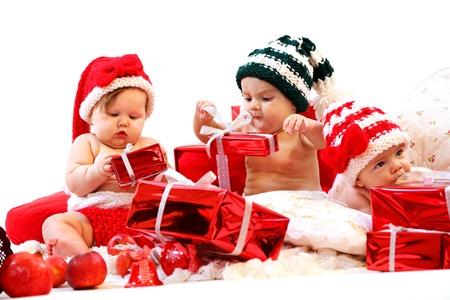 Drie baby's in xmas kostuums spelen met geschenken over witte achtergrond