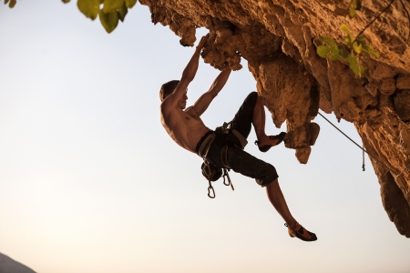 Rock climber of a cliff against sky at sunset