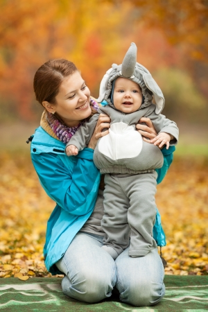 Portrait of young woman and her baby boy dressed in elephant costume in autumn park