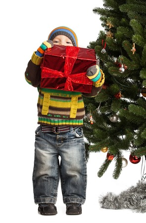 Cute little boy with gift near Christmas tree over white photo