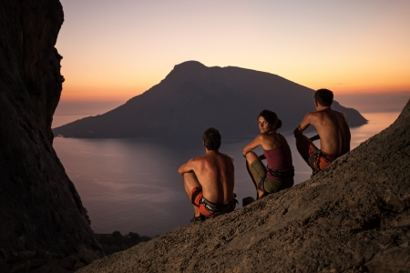 safety harness: Three rock climbers wearing safety harness having rest at sunset  With picturesque view of Telendos Island in front  Kalymnos Island, Greece  Stock Photo