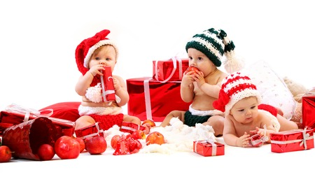 Three babies in xmas costumes playing with gifts over white background photo