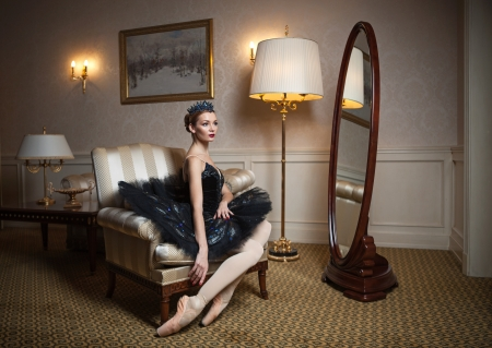 Ballerina in black tutu sitting in armchair in luxury interior photo