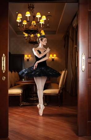 Ballerina in black tutu standing on pointes in doorway in luxury interior photo