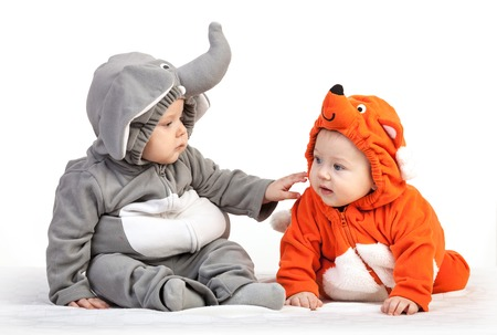 Two baby boys dressed in animal costumes playing over white