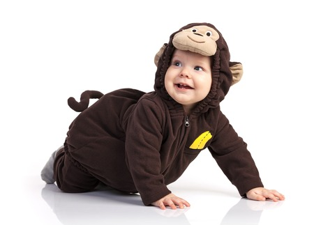 roztomilý: Roztomilý chlapeček v opičím kostýmu vzhlédl přes bílé Reklamní fotografie