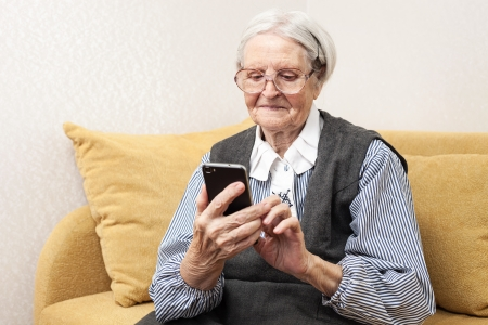 Senior woman using mobile phone while sitting on sofa photo