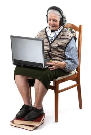 Senior woman using laptop computer isolated on white photo
