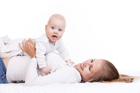 Smiling young woman holding baby son while lying on back photo