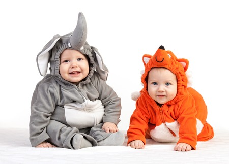 Two baby boys dressed in animal costumes over white photo