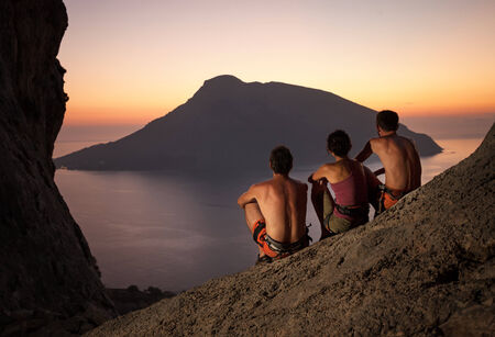 Three rock climbers wearing safety harness having rest at sunset photo
