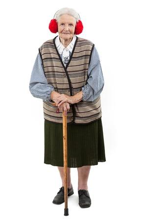 faux: Vecchia donna con un bastone che indossa rosso finto pelliccia cuffie su bianco Archivio Fotografico