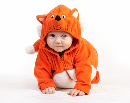 Baby boy in fox costume looking at camera over white