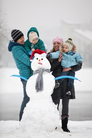 Caucasian family with two sons beside snowman outdoors photo