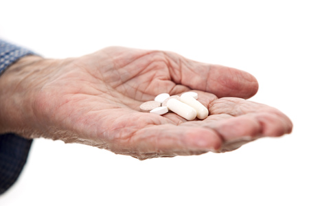 Closeup of senior hand holding medications over white
