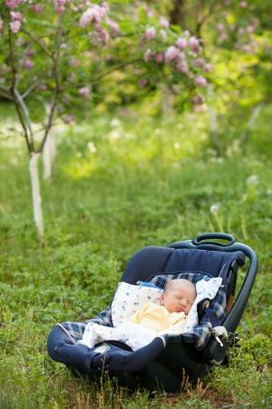 Newborn boy sleeping in car seat outdoors photo