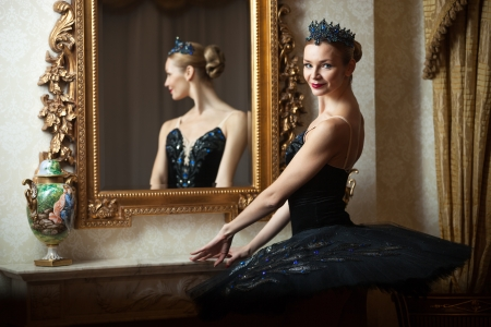 Ballerina in black tutu standing in front of mirror photo