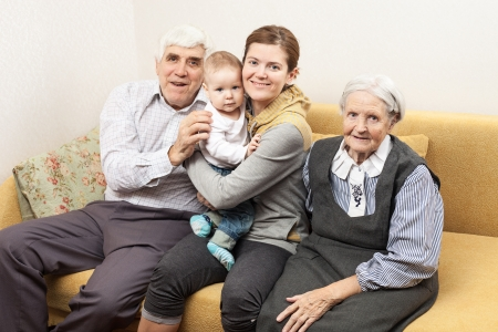 Four generation family sitting on sofa at home photo