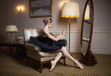 Ballerina in black tutu sitting in armchair in front of mirror and taking self portrait with camera on her cell phone photo