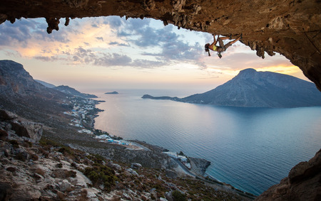 Female rock climber against picturesque view of Telendos\ Island at sunset Kalymnos Island, Greece