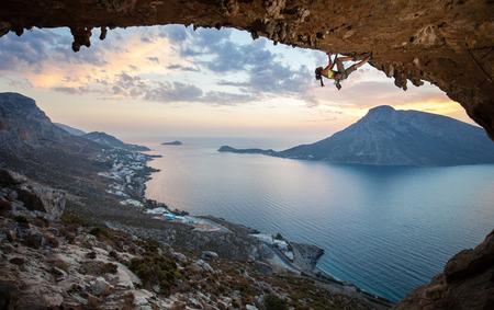 Femmina scalatore contro suggestiva vista di Telendos isola al tramonto Kalymnos, Grecia Archivio Fotografico - 25627491