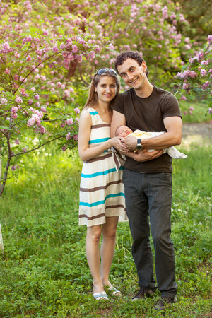 Happy young couple with newborn son outdoors in spring photo