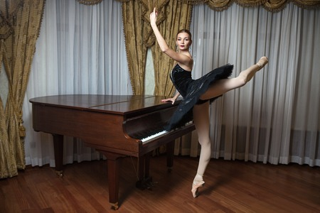 black toes: Ballerina in black tutu standing on pointes at the grand piano Stock Photo