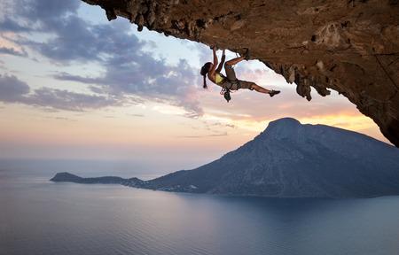 若い女性ロック ・ クライマー日没時、カリムノス島, ギリシャ