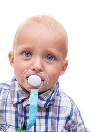 Closeup of cute blonde blue-eyed little boy with a pacifier over white background photo