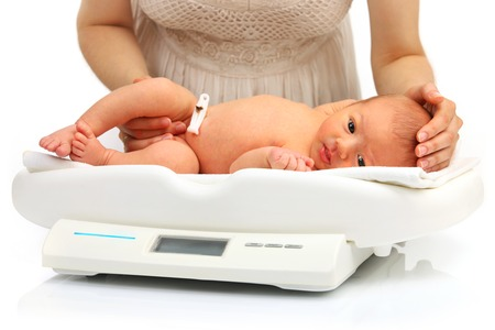 Mother and her newborn baby on a weight scale over white background