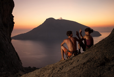 Two rock climbers having rest at sunset  Climbers giving high five and cheering  With picturesque view of Telendos Island in front  Kalymnos Island, Greece  photo