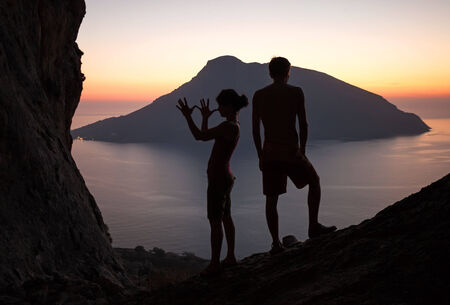 Silhouettes of two young people having fun at sunset, Kalymnos island, Greece photo