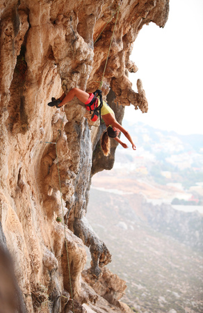 lead rope: Young female rock climber resting while hanging on rope