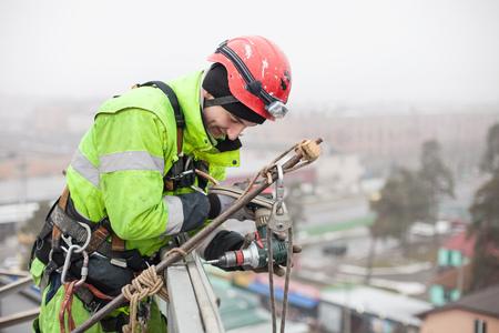 Alpinista przemysłowy na dachu budynku