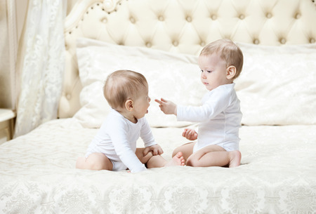 Two baby boys playing on bed at home photo