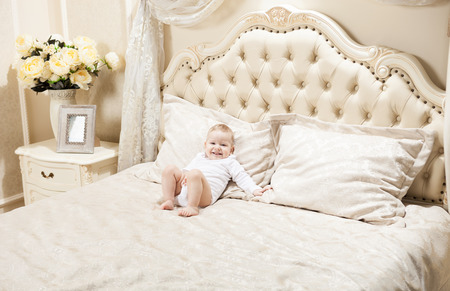 Little boy lying on bed at home and smiling photo