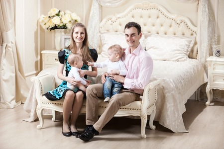 riches adult: Young happy family with two baby boys at home Stock Photo