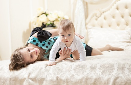 Young Caucasian mother and baby son on bed at home photo