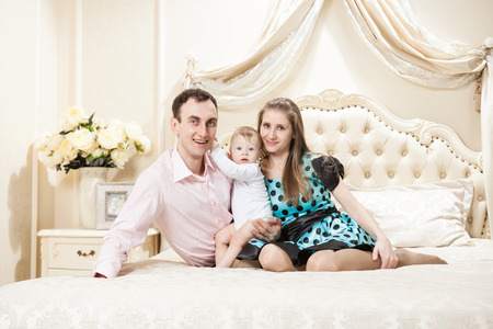 Young happy family with a baby on bed at home photo