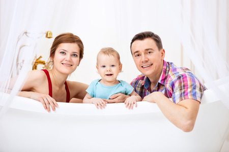 Happy young couple with son sitting in bath