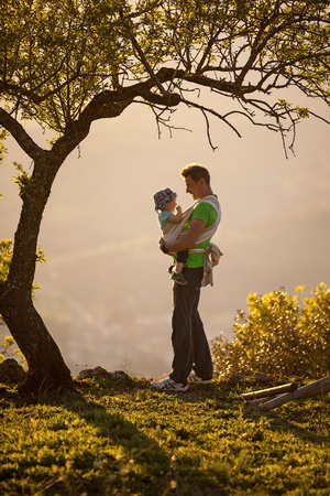 Father carrying his son in sling outdoors photo