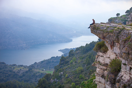 mountain man: Young man sitting on edge of cliff and looking at river below Stock Photo