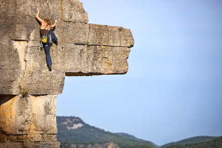 Young female free climber on face of a cliff