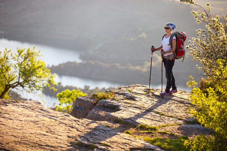 Hiker relaxing on cliff and enjoying valley view photo