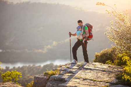 Hiker with baby relaxing standing on cliff against beautiful view photo