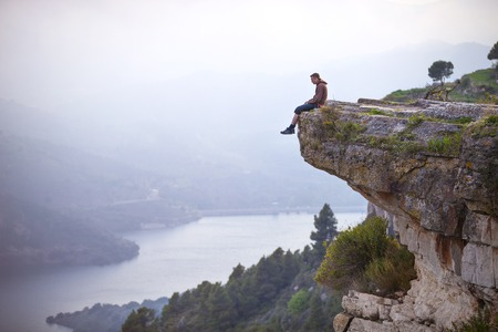 Young man sitting on edge of cliff and looking at river below Stock Photo