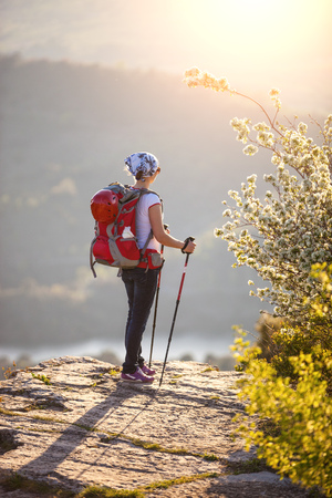 Young female hiker standing on cliff and enjoying valley view photo