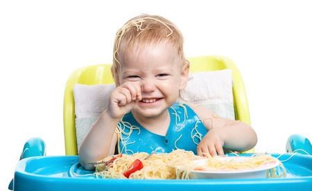 Little blond boy eating spaghetti and laughing